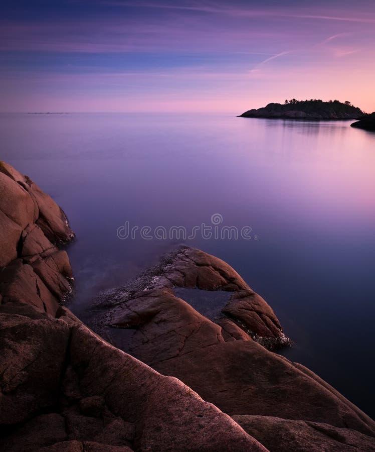 Isla y roca en el mar p?rpura lechoso foto de archivo libre de regalías