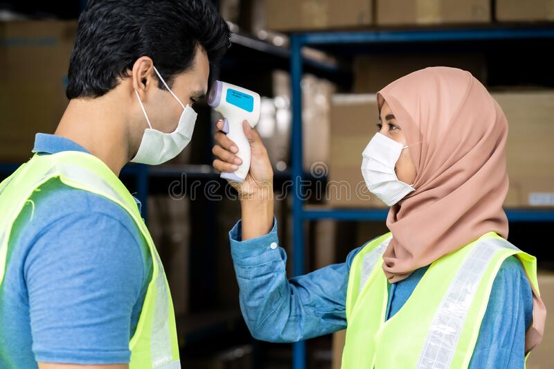Islam Muslim asian warehouse worker take temperature to another worker stock photography
