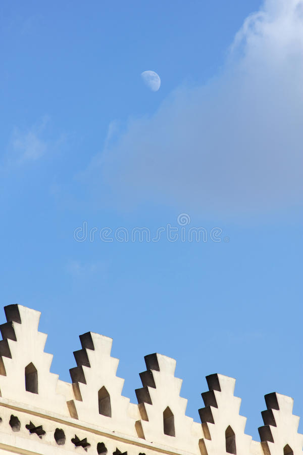 Islamic art with moon in egypt. Islamic art of an old vintage mosque located in cairo in egypt and the moon in blue sky background royalty free stock images
