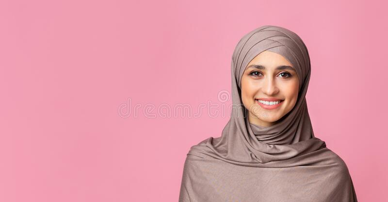 Portrait of smiling islamic woman in hijab over pink background stock photo