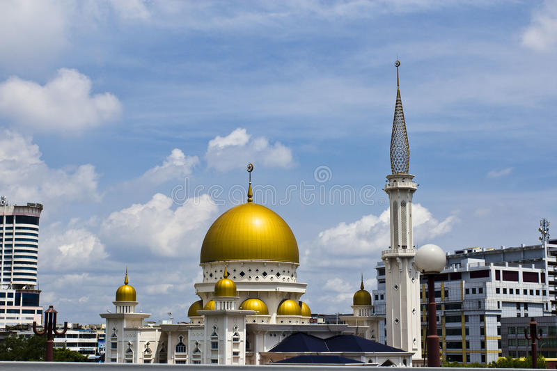 Islamic mosque, Klang, Malaysia. A vintage medieval golden dome islamic mosque on a river bank with reflection, on a blue cloudy day in the Royal Town of Klang stock photo