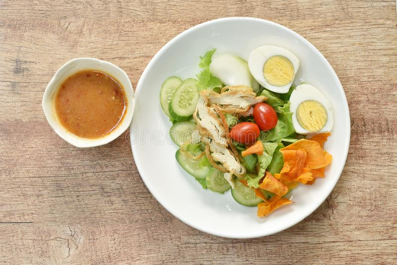 Islamic salad vegetable and boiled egg topping crispy fried taro dressing sweet bean sauce halal food on plate. Islamic salad vegetable and boiled egg topping stock photos