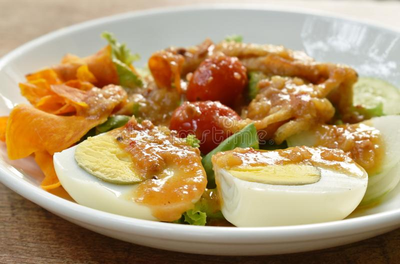 Islamic salad vegetable and boiled egg topping crispy fried taro dressing sweet bean sauce halal food on plate. Islamic salad vegetable and boiled egg topping stock photography