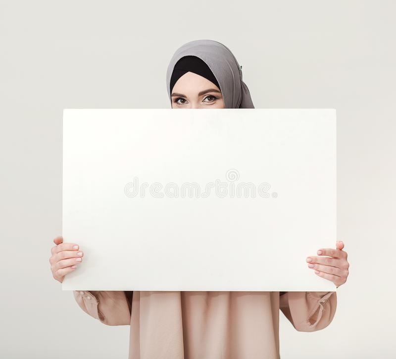 Islamic woman with blank board on white royalty free stock photos
