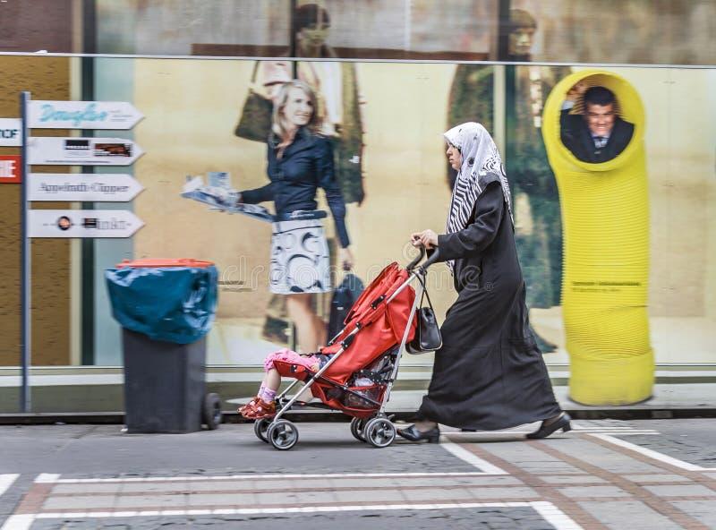 Islamische Frau mit ihrem Kind in einem Buggy stockfotos