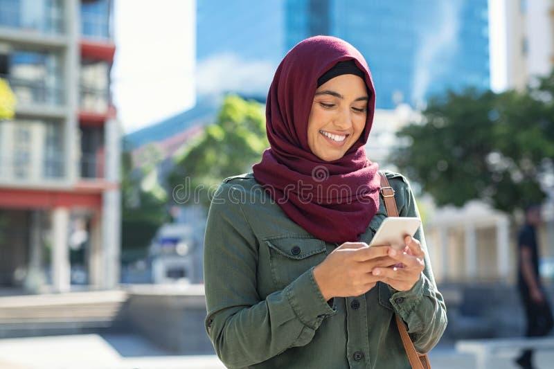 Islamisk kvinna i hijab genom att använda telefonen royaltyfria bilder