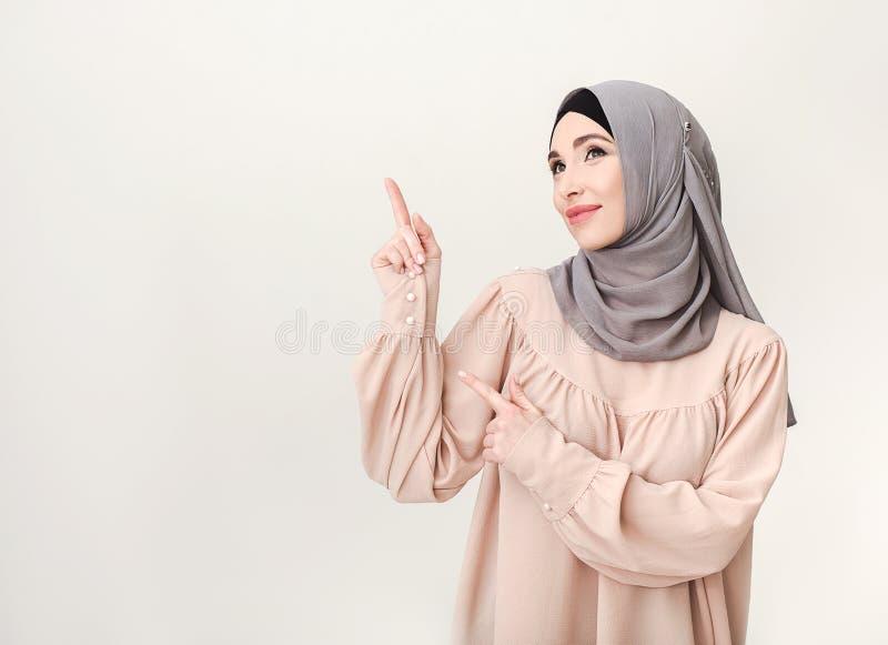 Islamisk kvinna i hijab som pekar på kopieringsutrymme arkivfoto