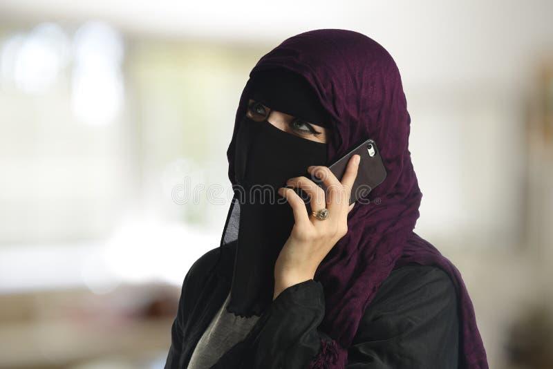 Islamisk kvinna som bär en burqa på mobiltelefonen arkivfoto