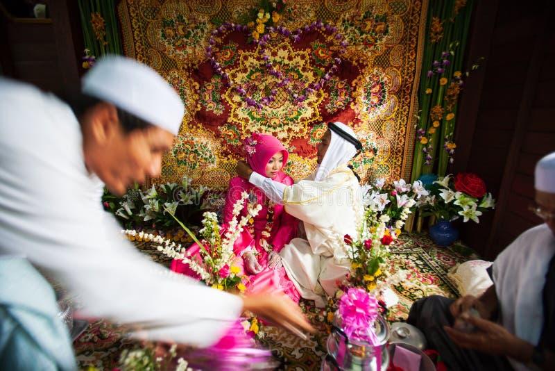 Islamiskt bröllop, brudgum som sätter en guld- halsband på brud Traditi royaltyfri fotografi