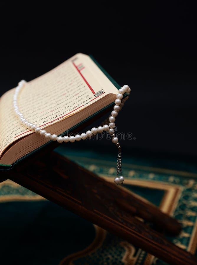 Islamitisch Heilig Boek Quran bij het houtsnijwerk rahle met rozentuinparels en gebeddeken op zwarte achtergrond Kuran het heilig royalty-vrije stock foto's
