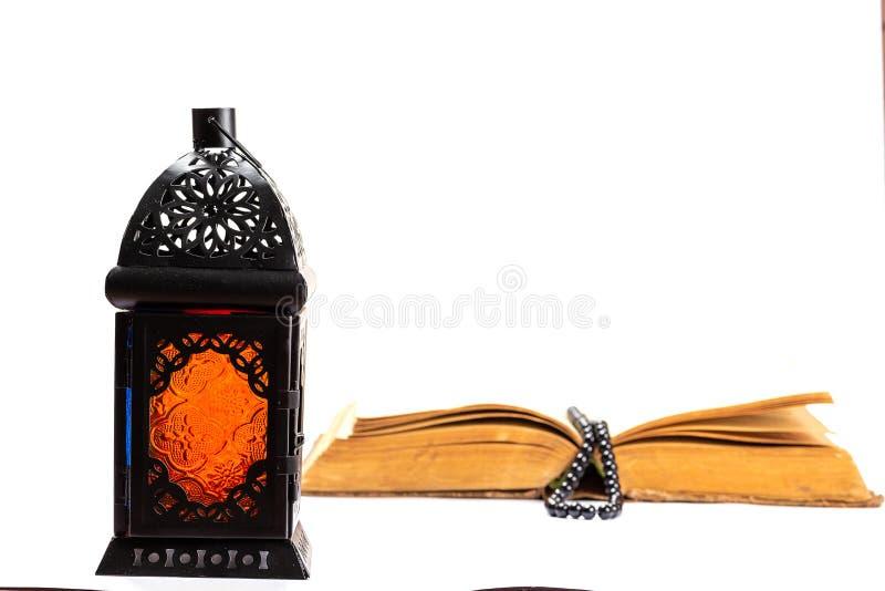 Islamitisch Heilig Boek Quran met rozentuinparels onder zacht licht op Witte Achtergrond met een glanzende lantaarn Fanus Ramadan stock afbeelding