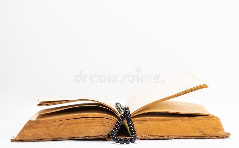 Islamitisch Heilig Boek Quran met rozentuinparels onder zacht licht op Witte Achtergrond Ramadanconcept Drie maanden stock afbeeldingen