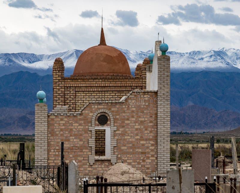 Islamitisch Mausoleum met bergen op achtergrond stock afbeeldingen