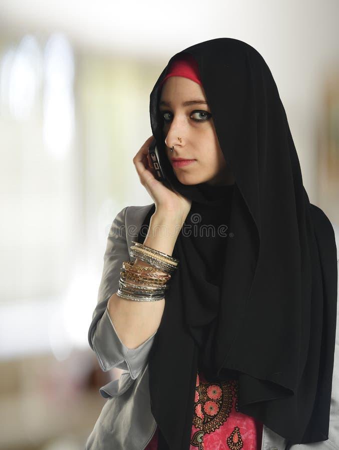 Islamitische vrouw die op de celtelefoon spreken stock afbeeldingen