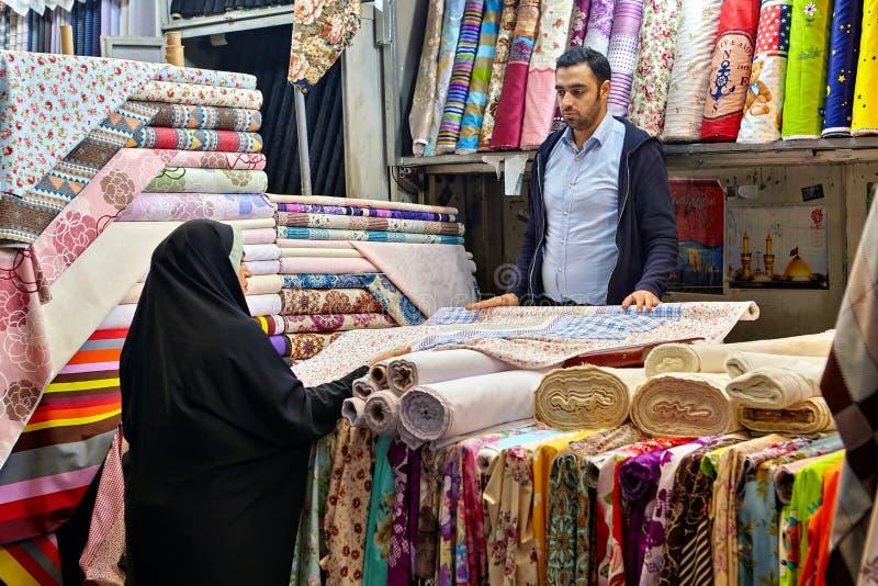 Islamska kobieta wybiera płótno w uroczystym bazarze Teheran, Iran obraz stock
