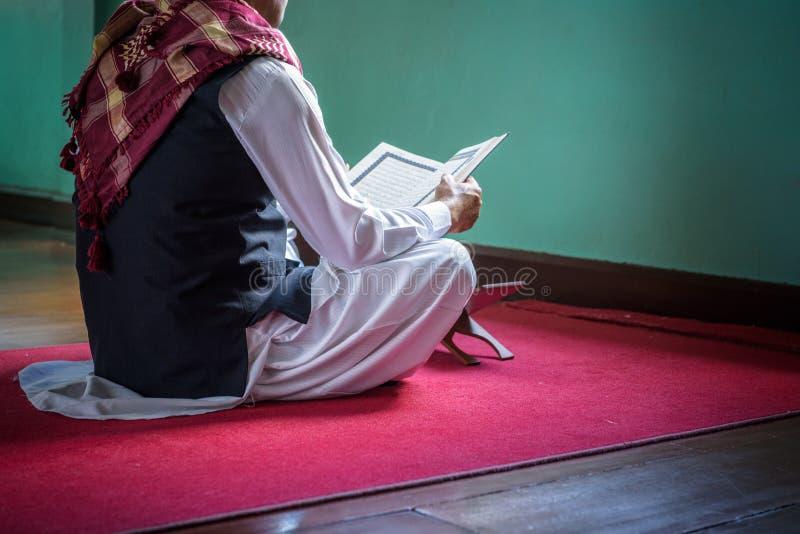 Islamu muzułmański mężczyzna w muzułmańskiej smokingowej czytelniczej świętej księdze Koran obrazy royalty free