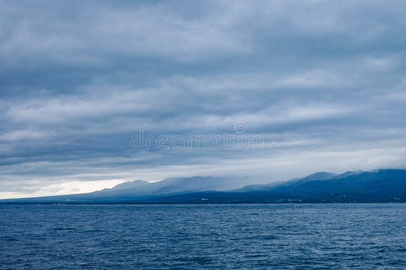 Island Across Body of Water Under Cloudy Sky royalty free stock photography