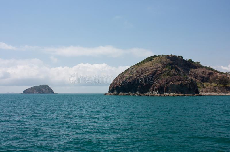 An island in the background and an outcrop at the Rosslyn Bay near Yeppoon in Capricorn area in Central Queensland, Australia. An island in the background and an royalty free stock image