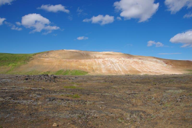 Island-Berg ockerhaltig und Grünes beleuchtet durch einen Sonnenstrahl stockbilder