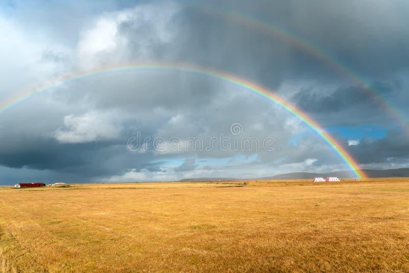 Island bygd under stormig himmel med regnbågar fotografering för bildbyråer