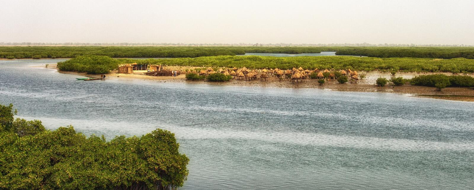 Island composed of shells with granaries on stilts out in the sea to protect from fire, Joal Fadiouth, Senegal stock image