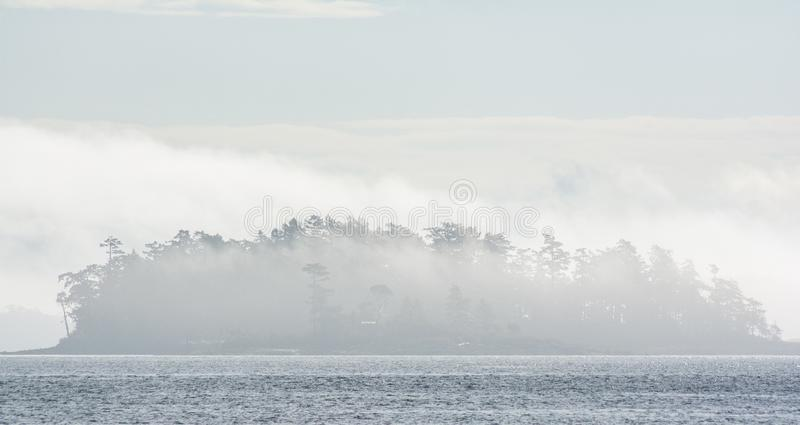 Island covered in mist in Pacific Northwest. An island covered in mist in the Pacific Northwest. foggy pacific north west view northwest forests sea pnw cascadia stock image