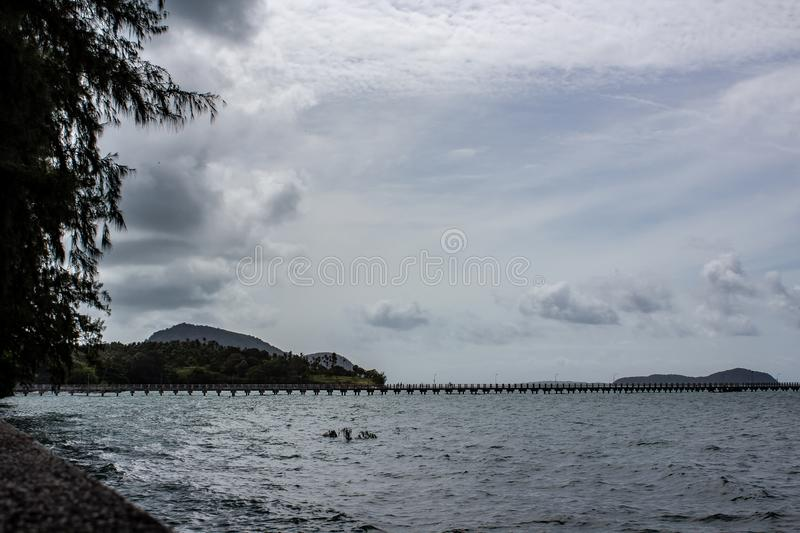 Island in the distance off the coast of Rawaii. Looking off the coast of Rawaii Phuket, Thailand. A mountain range cuts over the horizon stock images