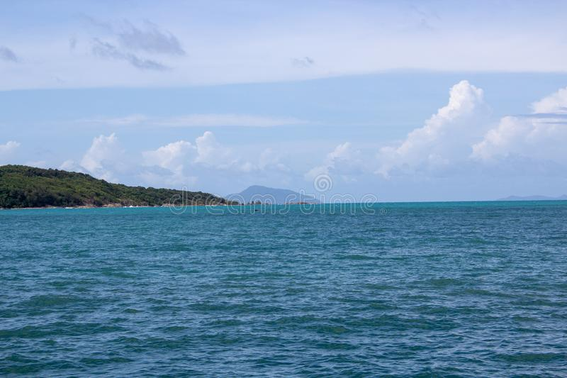 Island in the distance off the coast of Rawaii. Looking off the coast of Rawaii Phuket, Thailand. A mountain range cuts over the horizon royalty free stock photos