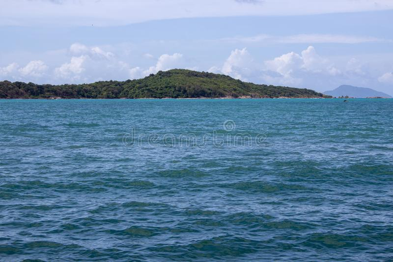 Island in the distance off the coast of Rawaii. Looking off the coast of Rawaii Phuket, Thailand. A mountain range cuts over the horizon stock photos
