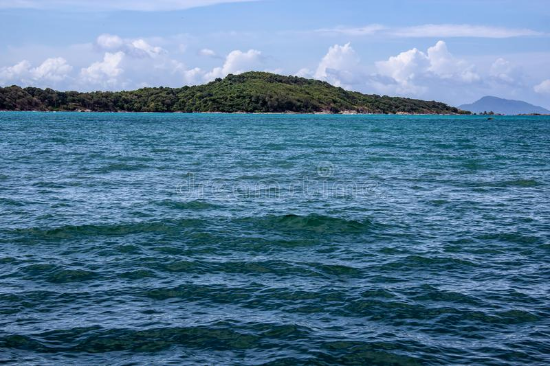 Island in the distance off the coast of Rawaii. Looking off the coast of Rawaii Phuket, Thailand. A mountain range cuts over the horizon royalty free stock photo