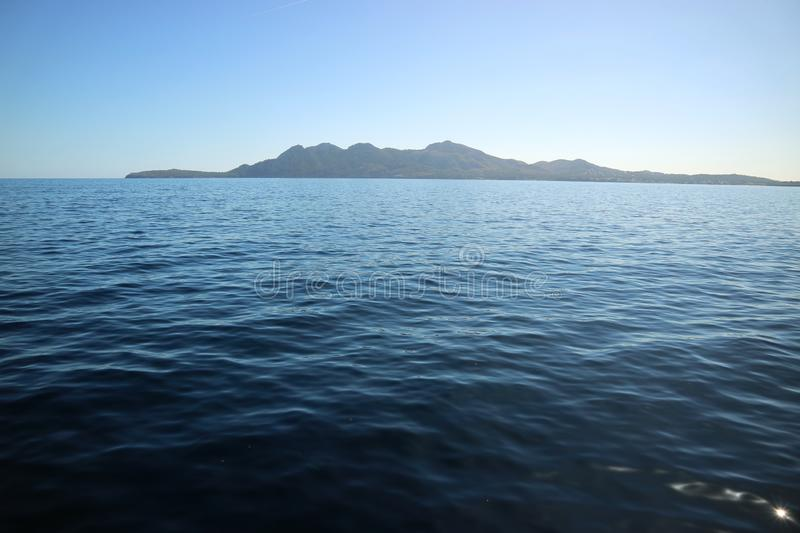 The island in the distance among the waves of the sea open water. For design Spain stock photos
