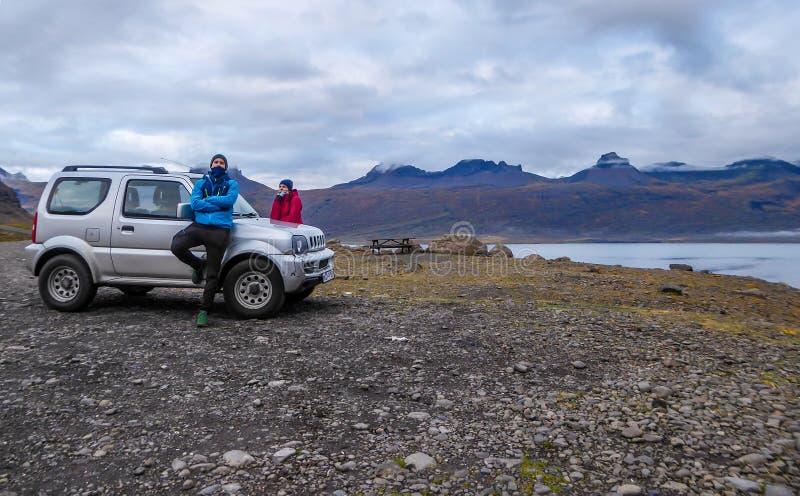 Island - ett par som lutar p? en bil arkivfoton