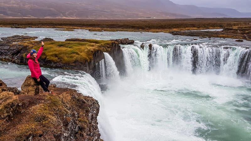 Island - flicka och en v?ldiga Godafoss arkivbild