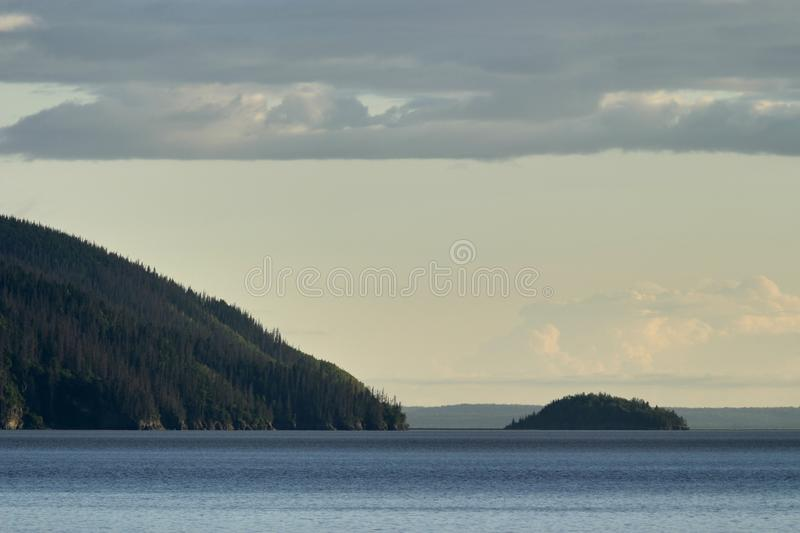 Island and Hilly Shoreline in Prince William Sound. Nature Scenic of Small Island off the Coast of Rolling Hills Covered with Trees in Early Morning with Cloudy stock image