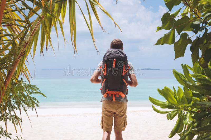 Young man with big backpack walking to the beach in a tropical holiday destination. Island hopping concept in the Maldives. Picture from back of a boy with a royalty free stock photos