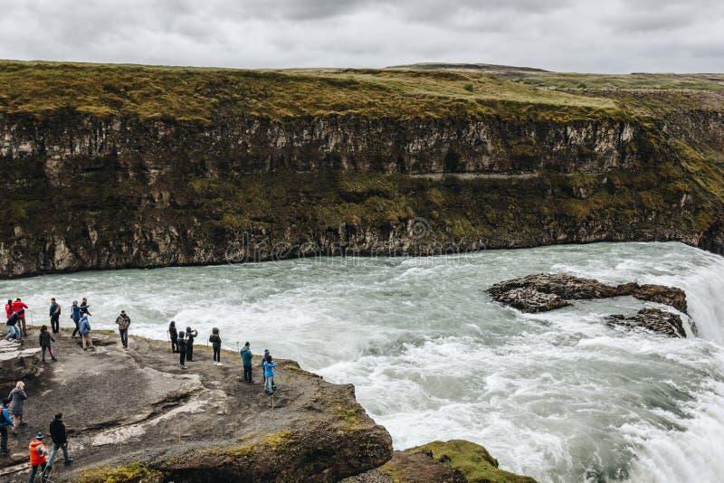 ISLAND - 20 JUNI 2018: grupp av turister nära vattenfallet Gullfoss under arkivbilder