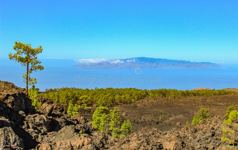 Island of La Gomera, soaring over the horizon, partly covered by the clouds. Bright blue sky. View from 1900 meters of altitude. royalty free stock image