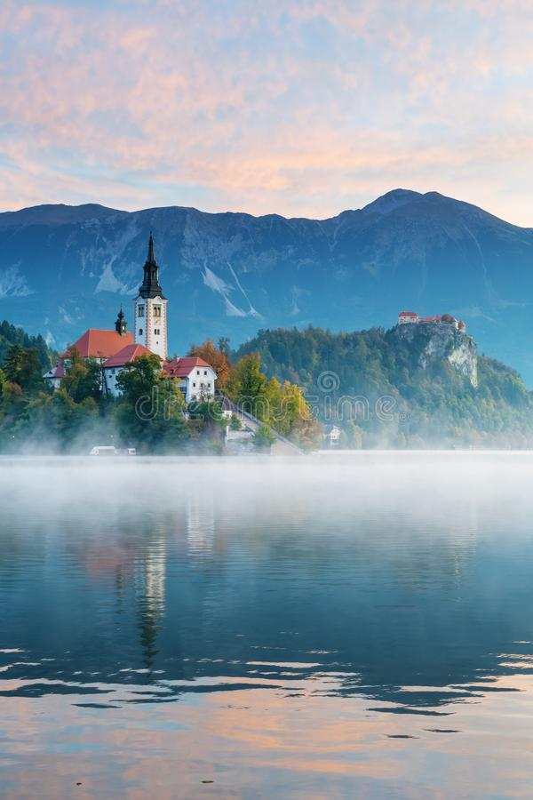 Island of lake Bled in the morning with castle and mountains in background. Beautiful morning view of lake Bled with beautiful sky during sunrise in autumn. Old stock image