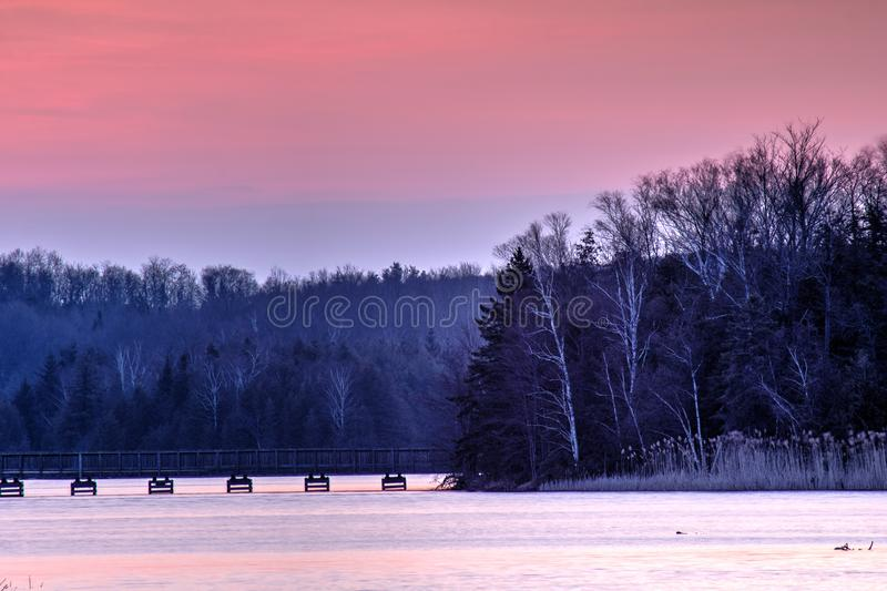 Island Lake Conservation Area In Subdued Early Light. The sun pops over the treeline at sunrise at the eastern end of Island Lake Conservation Area in stock photography