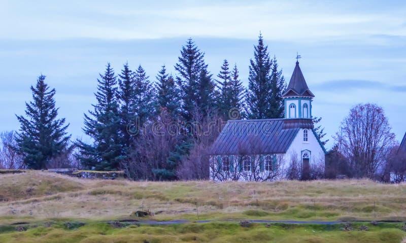 Island - lite kyrka bredvid skogen arkivbilder