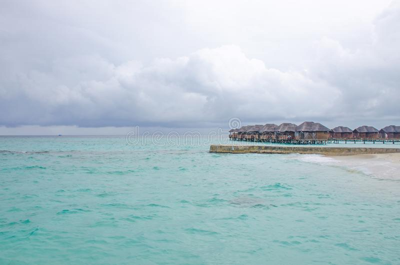 The island of Maldives of the house on Fiholhohi water a landscape the beach with blue water of the Indian Ocean in cloudy day royalty free stock photos