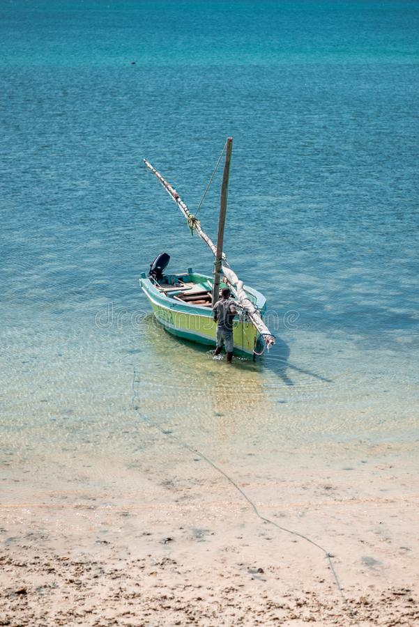 A fisherman at a small fishing boat moored in the shallow water at the beach. stock image