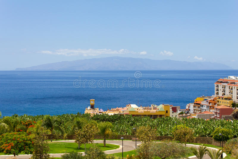 Island in the ocean. Greenery palm trees, colorful buildings of the city. All of this overlooking the ocean. On the horizon is located the island of La Gomera stock images