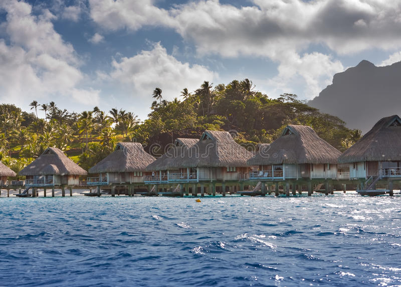 Island with palm trees and small houses on water in the ocean and mountains on a background stock photos