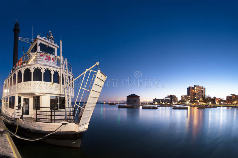 The Island Queen. An evening view of the Island Queen tour ferry against a blue twilight sky and the Kingston, Ontario, Canada waterfront cityscape royalty free stock photography