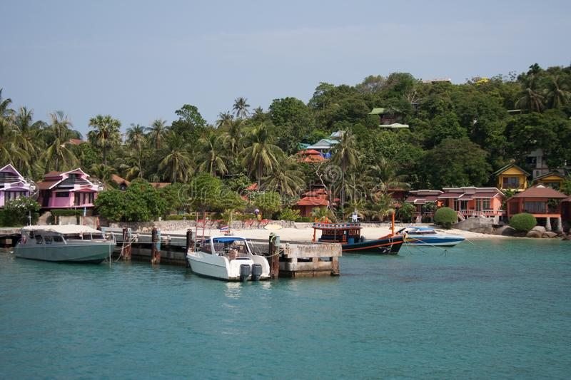 Island riviera with boats near pier, palms and bungalows stock photo