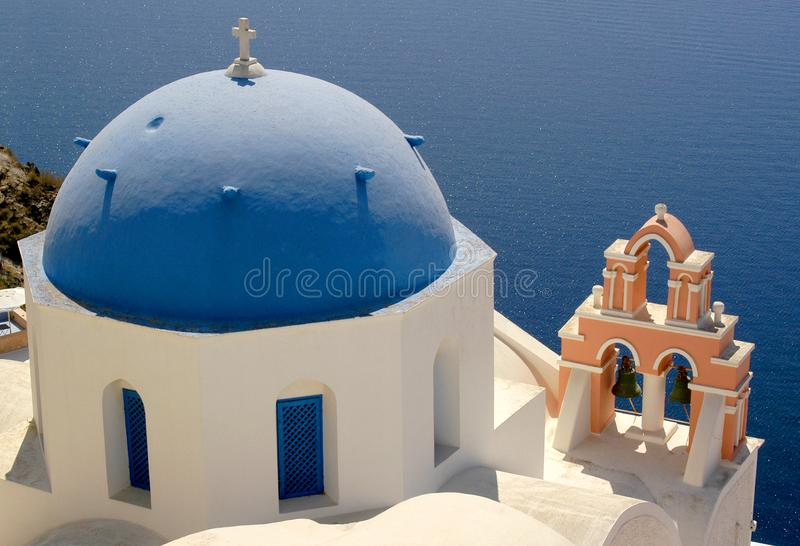 The island of Santorini offers breathtaking views over the ocean from colorful blue dome churches. This is one of the many blue dome churches with many bells on royalty free stock photography