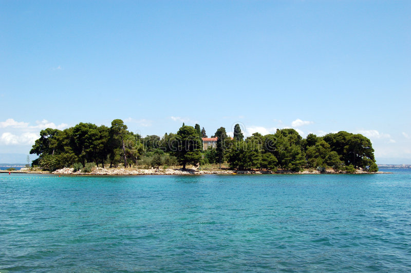 Island on sea. Small island in the Adriatic sea covered by a thick pine forest, surrounded by the blue sea and the blue sky. Galevac (Skoljic) near Preko on stock photos