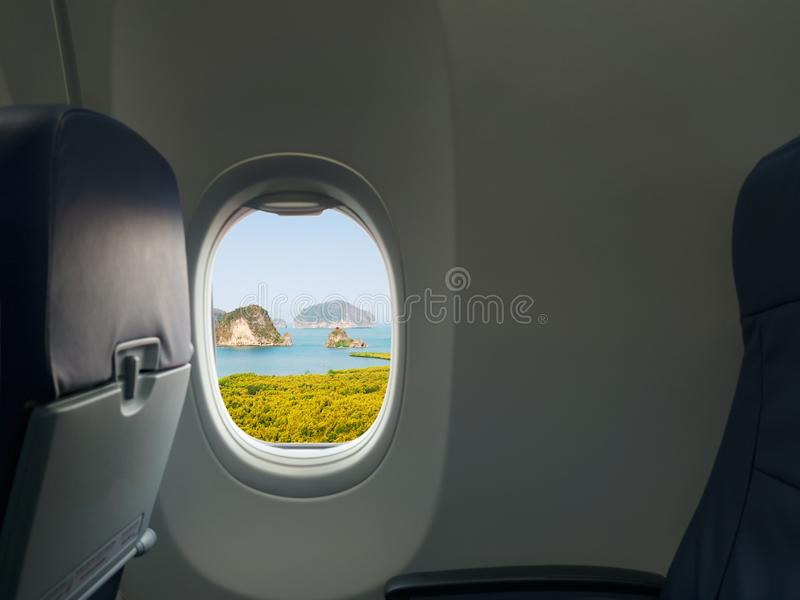 Island, sea and mountain view from window of airplane. Travel, vacation and journey concept stock photo