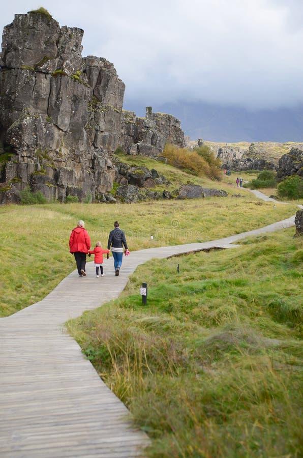 Island - September, 2014 - en familj går i guld- cirkeltur i Island nära loppfläckselfoss arkivfoton